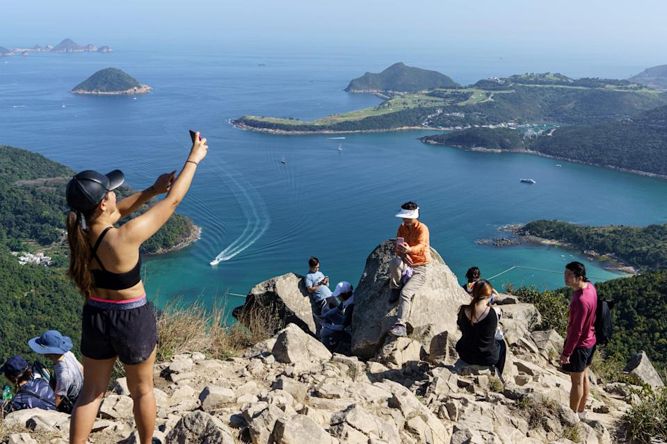 Representative: In this 29 February 2020 photo, hikers take pictures on High Junk Peak overlooking Clearwater Bay in the Tsuen Kwan O area of Hong Kong (AFP via Getty Images)