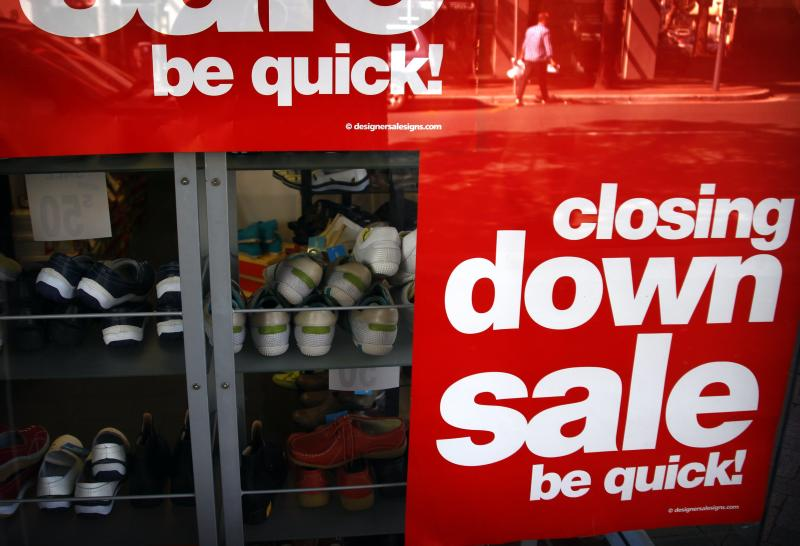 A customer is reflected in a window as he walks away from a shoe store that is having a sale before closing down in Sydney