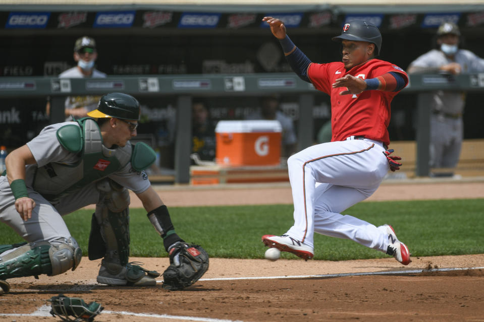 Minnesota Twins Jorge Polanco, right, slides past Oakland Athletics catcher Sean Murphy to score during the third inning of a baseball game, Sunday, May 16, 2021, in Minneapolis. Originally called out by home plate umpire John Libka, Polanco was called safe after review. (AP Photo/Craig Lassig)