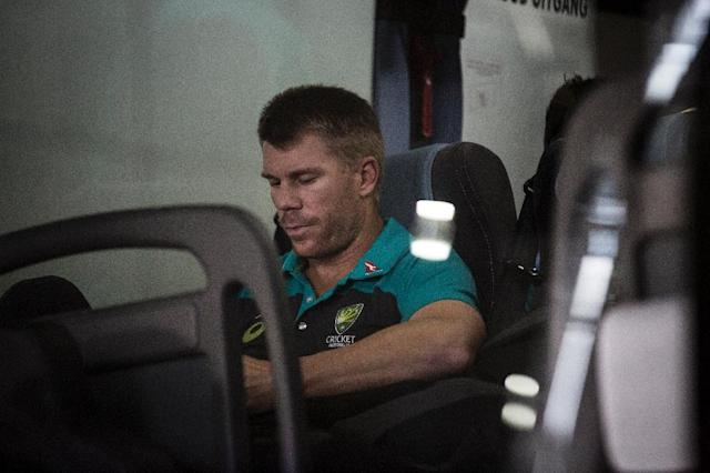 Former vice-captain David Warner of the Australian Cricket Team sits in the shuttle bus as he arrives at OR Tambo International Airport after the team was caught cheating in the Sunfoil Test Series between between Australia and South Africa on March 27, 2018. (AFP Photo/GULSHAN KHAN )