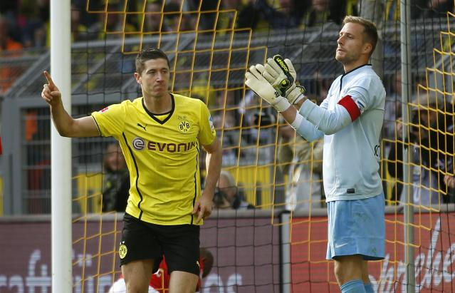Borussia Dortmund's Robert Lewandowski (L) celebrates a goal, while Freiburg's goalkeeper Oliver Baumann reacts during the German first division Bundesliga soccer match in Dortmund September 28, 2013. REUTERS/Ina Fassbender (GERMANY - Tags: SPORT SOCCER) DFL RULES TO LIMIT THE ONLINE USAGE DURING MATCH TIME TO 15 PICTURES PER GAME. IMAGE SEQUENCES TO SIMULATE VIDEO IS NOT ALLOWED AT ANY TIME. FOR FURTHER QUERIES PLEASE CONTACT DFL DIRECTLY AT + 49 69 650050
