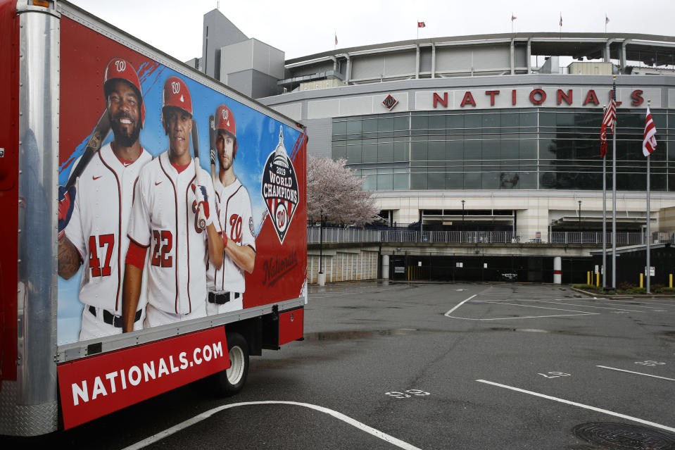 In this Wednesday, March 25, 2020, photo, a truck sits in a largely empty player's parking lot at Nationals Park in Washington. With the start of the Major League Baseball season indefinitely on hold because of the novel coronavirus pandemic, ballparks will be empty Thursday on what was supposed to be opening day. (AP Photo/Patrick Semansky)