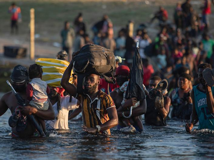 Migrants, many from Haiti, wade across the Rio Grande river from Del Rio, Texas, to return to Ciudad Acuña, Mexico, Monday, Sept. 20, 2021, to avoid deportation from the U.S. The U.S. is flying Haitians camped in a Texas border town back to their homeland and blocking others from crossing the border from Mexico.