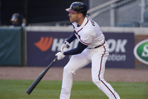 Atlanta Braves Freddie Freeman (5) follows through with a game-winning base hit against the Cincinnati Reds in the 13th inning during Game 1 of a National League wild-card baseball series, Wednesday, Sept. 30, 2020, in Atlanta. The Atlanta Braves won 1-0. (AP Photo/John Bazemore)