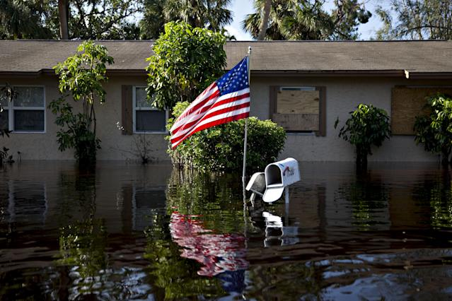 <p>A U.S. flag flies outside a flooded home in Bonita Springs, Fla., on Sept. 12, 2017. Hurricane Irma smashed into Southern Florida as a Category 4 storm, driving a wall of water and violent winds ashore and marking the first time since 1964 the U.S. was hit by back-to-back major hurricanes. (Photo: Daniel Acker/Bloomberg via Getty Images) </p>