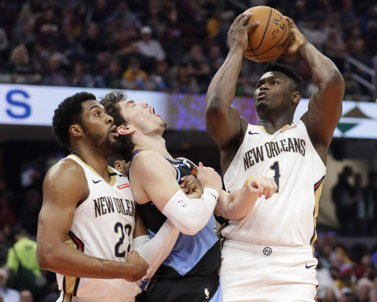 New Orleans Pelicans' Zion Williamson, right, shoots against Cleveland Cavaliers' Cedi Osman, center, during the second half of an NBA basketball game Tuesday, Jan. 28, 2020, in Cleveland. Derrick Favors, left, watches. (AP Photo/Tony Dejak)