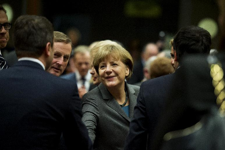 German Chancellor Angela Merkel (C) shakes hands with officials during a round table meeting, part of the European Council Summit, at EU headquarters in Brussels on February 12, 2015 (AFP Photo/Alain Jocard)