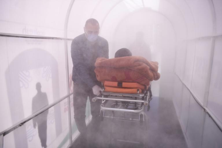A health worker walks a patient through a disinfection chamber set up in front of a hospital in Mitrovica, Kosovo