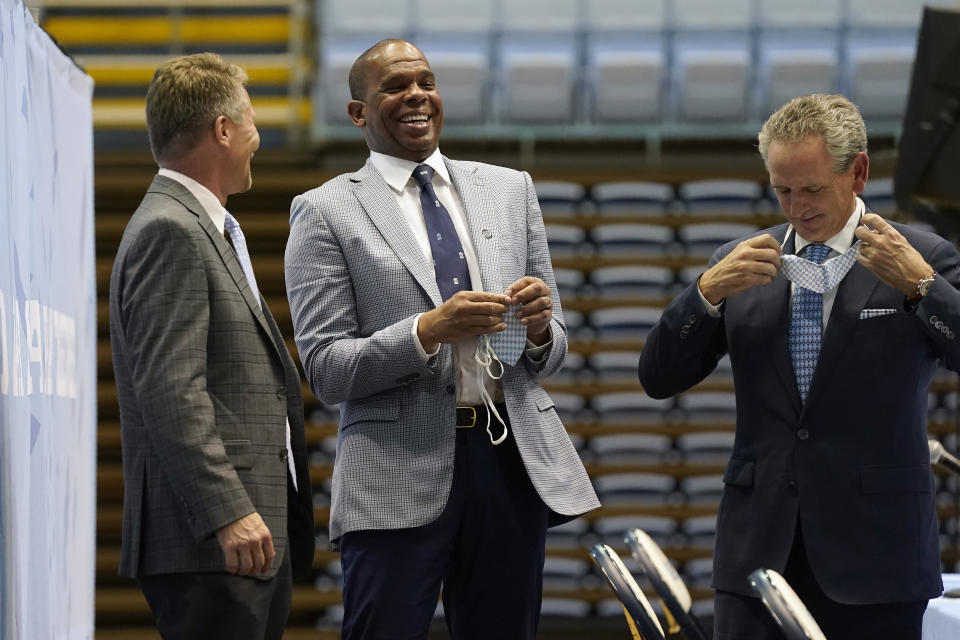 North Carolina head coach Hubert Davis, center, laughs with chancellor Kevin Guskiewicz, left, and athletic director Bubba Cunningham following a news conference at the University of North Carolina in Chapel Hill, N.C., Tuesday, April 6, 2021. Davis was named the Tar Heels new NCAA men's basketball coach following the retirement of Roy Williams. (AP Photo/Gerry Broome)