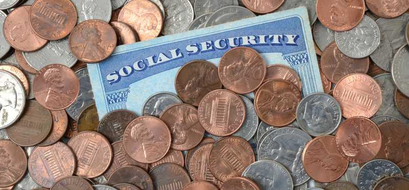 Social security card piled with coins.