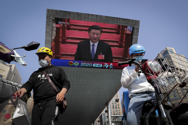 Food delivery workers wearing face masks to protect against the spread of the new coronavirus prepare to delivery foods near a TV screen showing Chinese President Xi Jinping attending the closing ceremony of the National People's Congress in a news report, in Beijing, China, Thursday, May 28, 2020. China's ceremonial legislature on Thursday endorsed a national security law for Hong Kong that has strained relations with the United States and Britain. (AP Photo/Andy Wong)