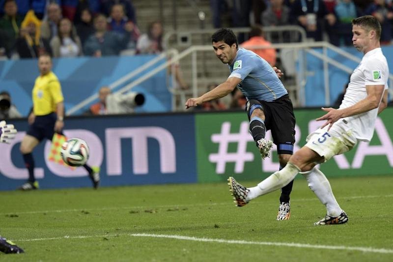 Nightmare | Suarez beats Cahill to score the goal which sent England home from Brazil (AFP/Getty Images)