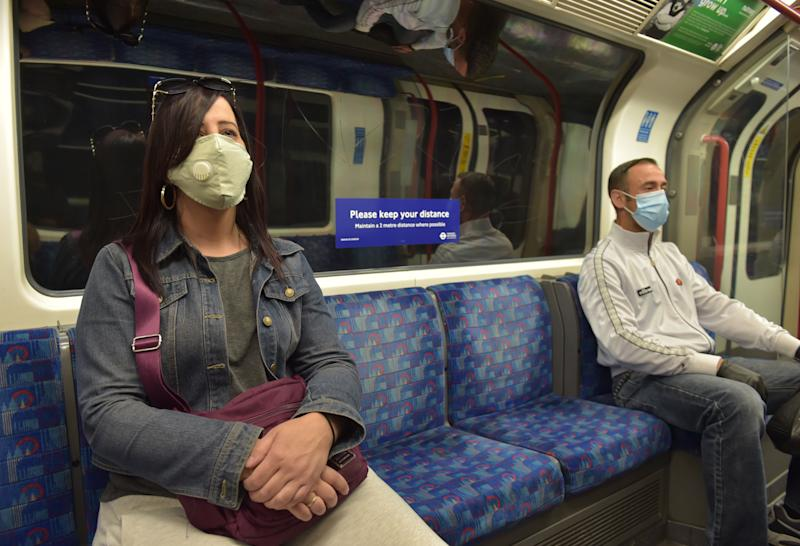 Passengers wear face masks on a Central Line underground train, following the announcement that wearing a face covering will be mandatory for passengers on public transport in England from June 15. (Photo by Nick Ansell/PA Images via Getty Images)