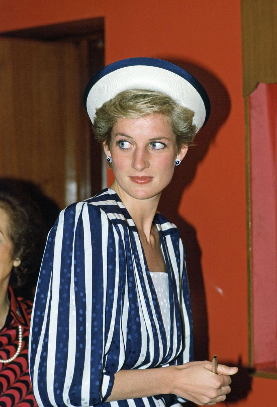 <p>During an official visit to Bahrain, Princess Diana wore a nautical-inspired look, featuring a navy and white striped dress and matching hat. </p>