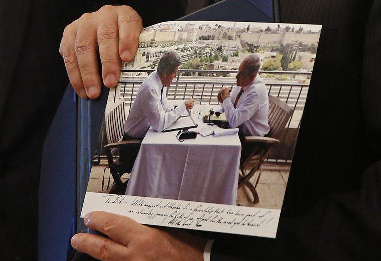 Israeli PM Benjamin Netanyahu shows a picture that was given to him as a gift by US Secretary of State John Kerry
