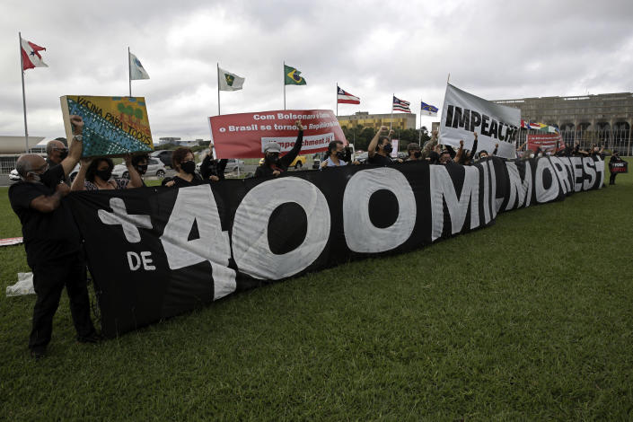 Demonstrators hold a banner referring to the milestone of 400,000 COVID-19 related deaths in Brazil as they protest the government's handling of the pandemic outside the National Congress in Brasilia, Brazil, Friday, April 30, 2021. (AP Photo/Eraldo Peres)