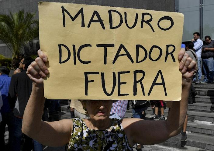 """The sign held by an anti-government activist at the rally where Juan Guaido spoke reads """"Maduro dictator out"""" (AFP Photo/Yuri CORTEZ)"""