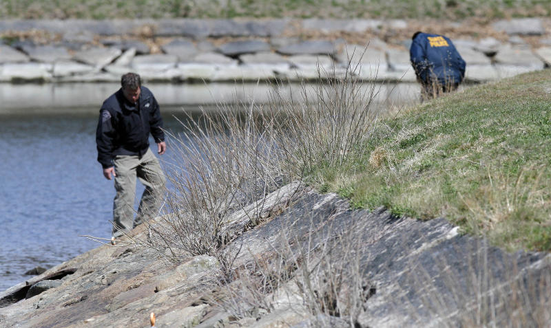 Police look along the bank of the Chestnut Hill Reservoir in Boston, where the body Boston College student Franco Garcia was recovered Wednesday, April 11, 2012. Garcia disappeared Feb. 22 after leaving a popular bar near the college. (AP Photo/Michael Dwyer)