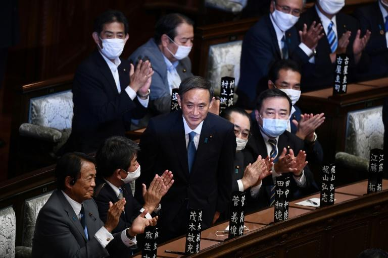 Suga bowed deeply as lawmakers applauded following the announcement