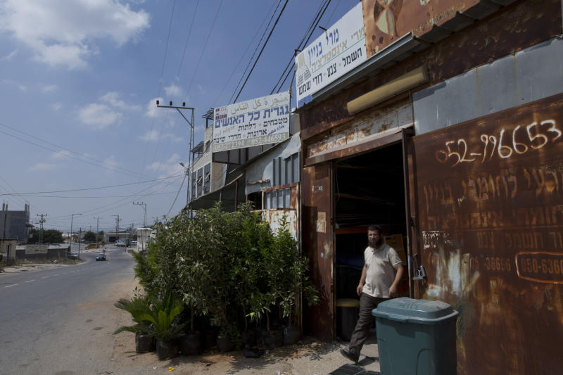 """In this Wednesday, Sept. 11, 2019 photo, a man walks out of a Palestinian carpentry shop under a sign in Arabic and Hebrew that reads, """"All the people's carpenter,"""" in the West Bank village of Mas'ha, west of Qalqiliya. The 2.5 million Palestinians living in the West Bank are unable to vote in Israel's elections next week, which could determine whether it annexes parts of the occupied territory and places their dreams of an independent state even further out of reach. The Palestinians expect little change regardless of who wins. (AP Photo/Nasser Nasser)"""