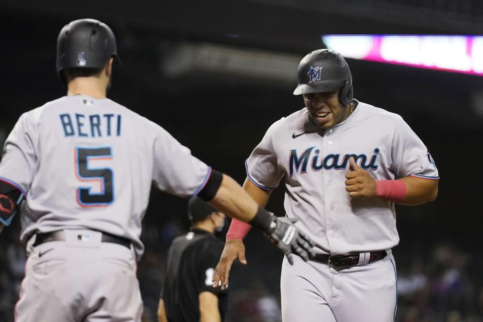 Miami Marlins' Jesus Aguilar, right, smiles as he celebrates with Jon Berti after scoring against the Arizona Diamondbacks during the seventh inning of a baseball game Thursday, May 13, 2021, in Phoenix. (AP Photo/Ross D. Franklin)
