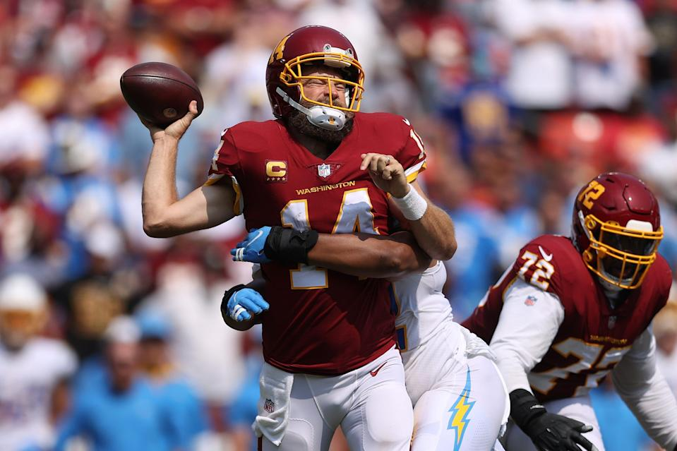 Ryan Fitzpatrick #14 of the Washington Football Team takes a hit against the Los Angeles Chargers during the second quarter at FedExField on September 12, 2021 in Landover, Maryland.