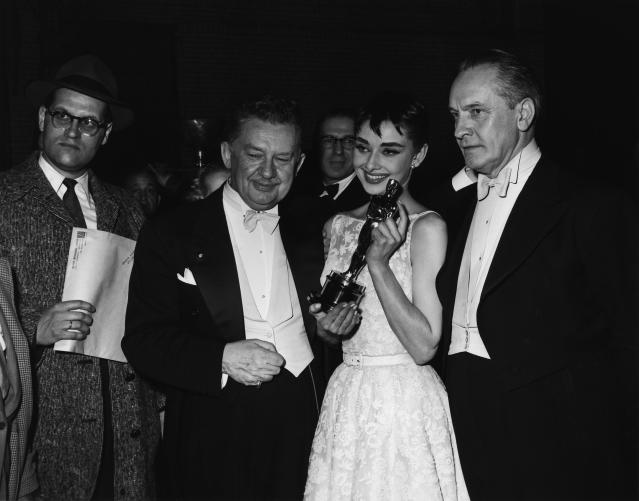 <p>Audrey Hepburn, wearing a Givenchy dress at the 26th Annual Academy Awards, holds her Award for Best Actress in a Leading Role for <em>Sabrina</em> at the Pantages Theater in Hollywood on March 25, 1954. (Photo: NBCU Photo Bank, Getty Images) <br><br></p>