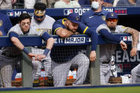 Milwaukee Brewers left fielder Christian Yelich, left and other players watch the game during the ninth inning of Game 3 of a baseball National League Division Series, Monday, Oct. 11, 2021, in Atlanta. The Atlanta Braves won 3-0. (AP Photo/John Bazemore)