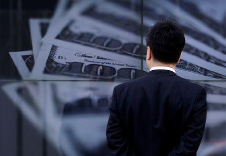 A businessman looks at a screen displaying a photo of U.S. 100 dollar bank notes in Tokyo