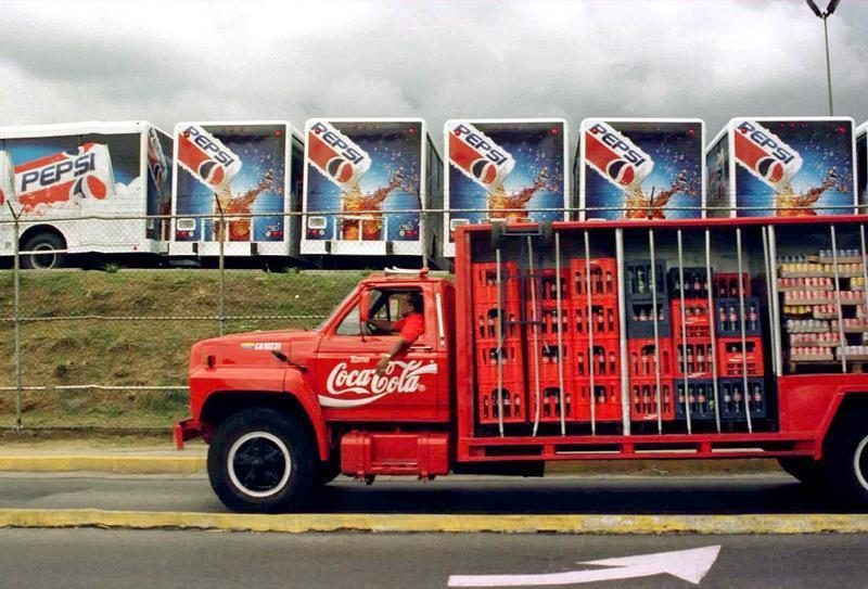 A Coca Cola truck passes in front of a Pepsi Co. parking lot filled with new Pepsi Cola trucks Decem..
