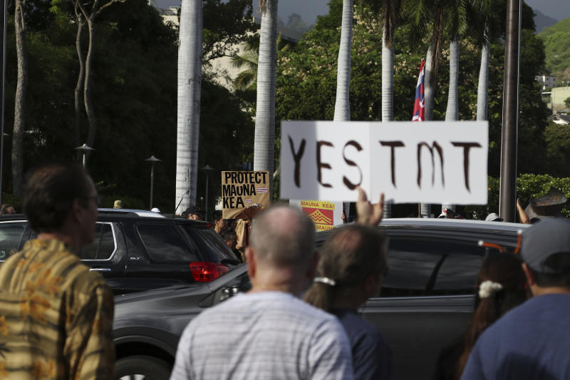 Supporters of the Thirty Meter Telescope, foreground, gather for a rally outside the Hawaii State Capitol in Honolulu on Thursday, July 25, 2019, as opponents of the telescope gather across the street. Supporters said the giant telescope planned for Hawaii's tallest mountain will enhance humanity's knowledge of the universe and bring quality, high-paying jobs, as protesters blocked construction for a second week. (AP Photo/Audrey McAvoy)