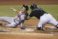 Miami Marlins catcher Sandy Leon (7) tags out Atlanta Braves' Max Fried at home during the third inning of a baseball game, Saturday, June 12, 2021, in Miami. (AP Photo/Wilfredo Lee)