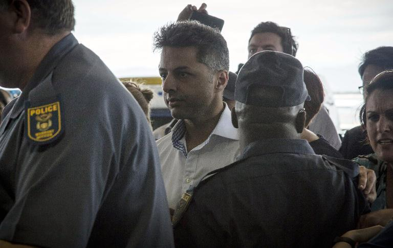 British businessman Shrien Dewani (centre) arrives at Cape Town International Airport on December 9, 2014 (AFP Photo/)