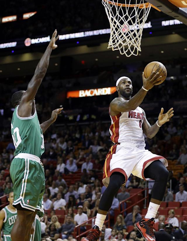 Miami Heat's LeBron James, right, shoots as Boston Celtics' Brandon Bass, left, defends during the first half of an NBA basketball game Saturday, Nov. 9, 2013, in Miami. (AP Photo/Lynne Sladky)