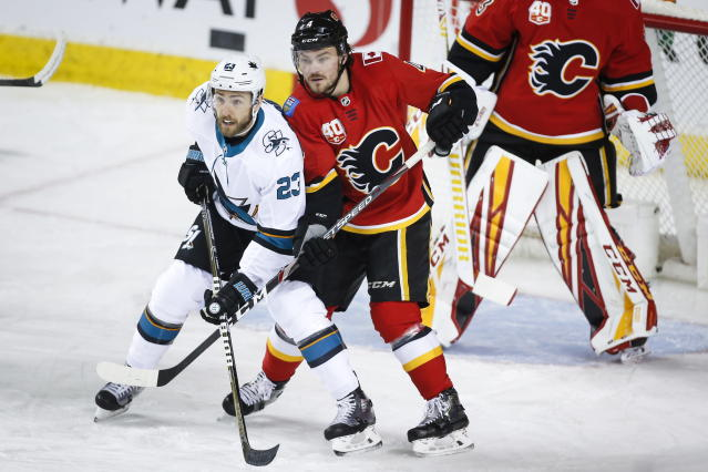 San Jose Sharks' Barclay Goodrow, left, and Calgary Flames' Rasmus Andersson fight for position during the first period of an NHL hockey game, Tuesday, Feb. 4, 2020 in Calgary, Alberta. (Jeff McIntosh/The Canadian Press via AP)