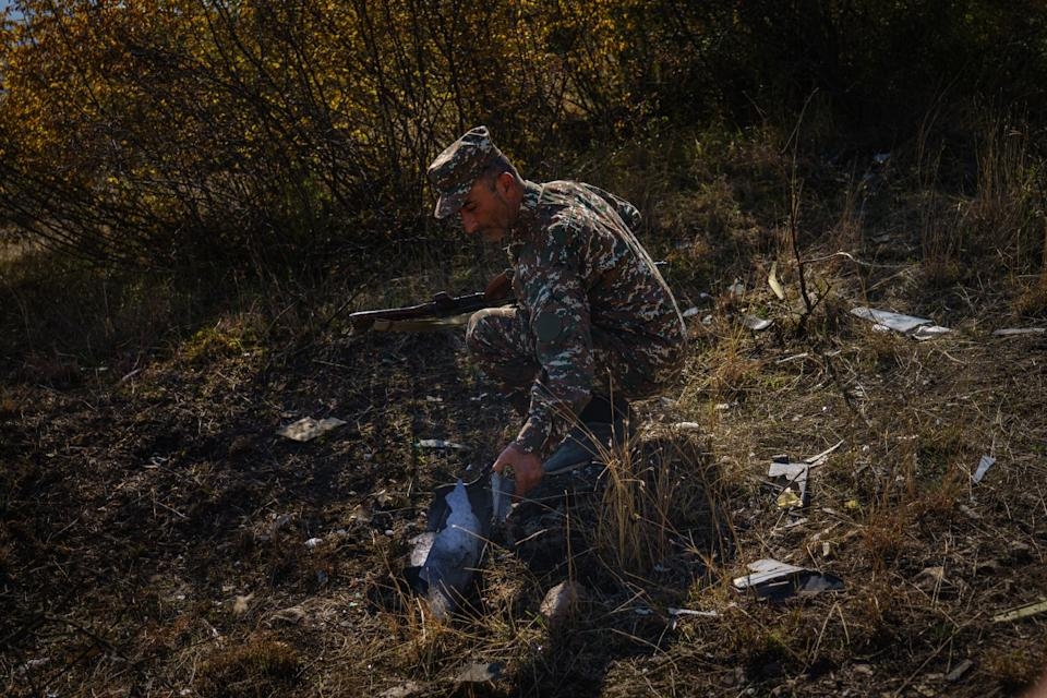 A man in fatigues examines a drone remnant on a hillside in Nagorno-Karabakh.