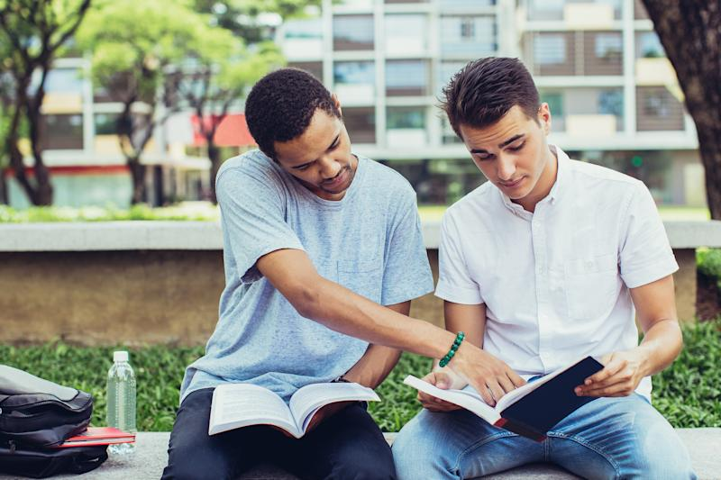 Two male college students study on campus in a courtyard.