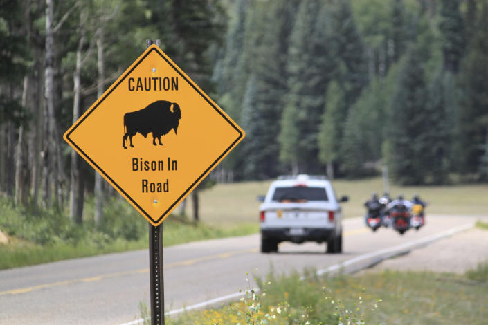 FILE - In this July 31, 2016, file photo, a park ranger and a group of motorcyclists pass a sign warning of bison within the Grand Canyon National Park in northern Arizona. The National Park Service is opening a rare opportunity for skilled volunteers to help reduce the population of bison that are roaming the far reaches of Arizona. Thousands of people are expected to apply for one of 12 spots to lethally remove bison later this year at Grand Canyon National Park. (AP Photo/Susan Montoya Bryan, File)