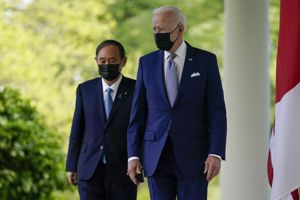 President Joe Biden, accompanied by Japanese Prime Minister Yoshihide Suga, walks from the Oval Office to speak at a news conference in the Rose Garden of the White House, Friday, April 16, 2021, in Washington. (AP Photo/Andrew Harnik)