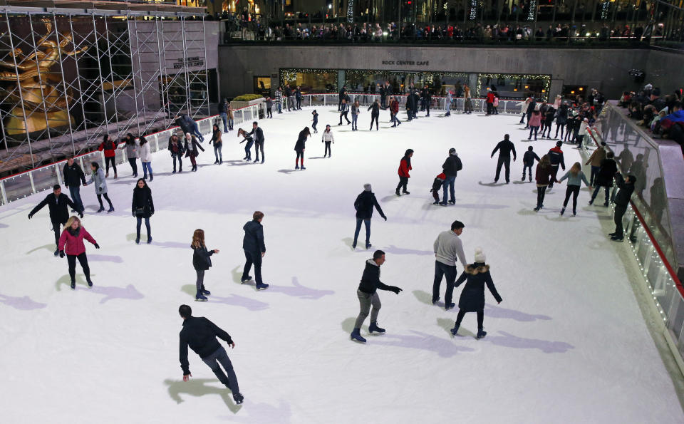 FILE- This Nov. 12, 2017 file photo shows skaters at the Rockefeller Center skating rink in New York. The iconic, sunken rink in midtown Manhattan is welcoming skaters Saturday, Nov. 21, 2020, as part of a tradition dating to the 1930s, according to the Rockefeller Center website.The rink is operating at a reduced capacity, with skate time limited to 50 minutes. Masks are required as a further pandemic safety measure. (AP Photo/Kathy Willens)