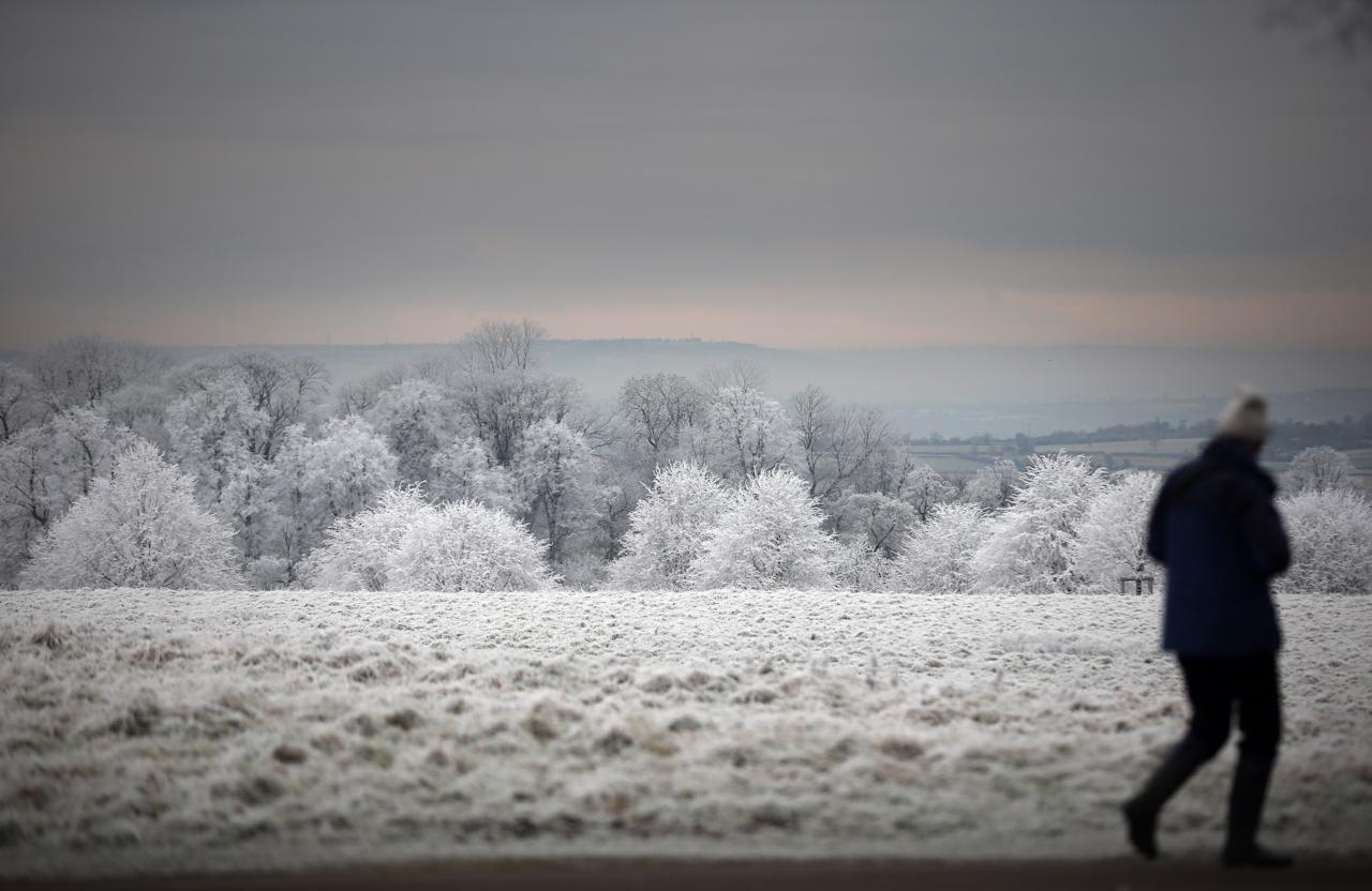 BATH, UNITED KINGDOM - DECEMBER 12:  A person is seen out walking as frost lingers on the trees at Dyrham Park on December 12, 2012 near Bath, England. Forecasters have warned that the UK could experience the coldest day of the year so far today, with temperatures dropping as low as -14C, bringing widespread ice, harsh frosts and freezing fog. Travel disruption is expected with warnings for heavy snow in some parts of the country.  (Photo by Matt Cardy/Getty Images)