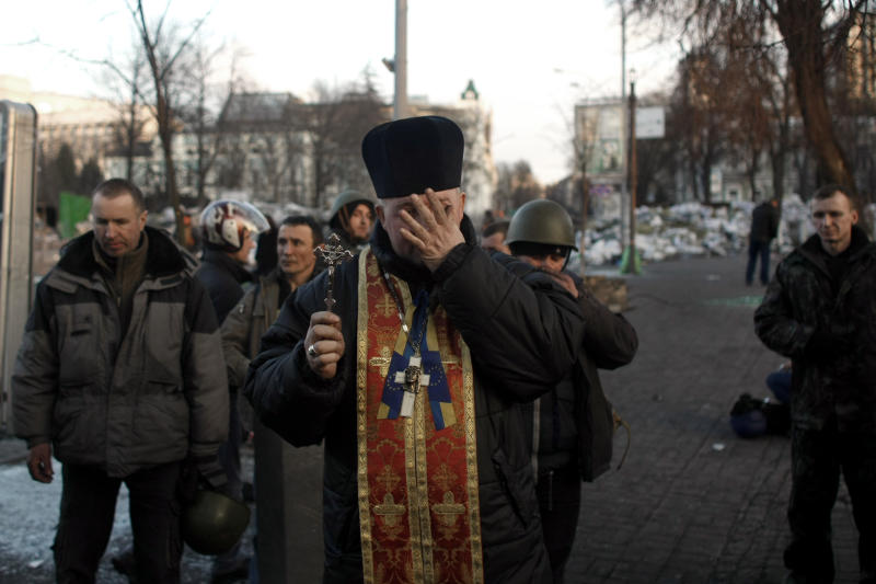 A priest is overcome with emotions as he holds a memorial service for protesters killed during clashes with the police, on the brinks of Independence Square in Kiev, Ukraine, Friday, Feb. 21, 2014. In a day that could significantly shift Ukraine's political destiny, opposition leaders signed a deal Friday with the country's beleaguered president that calls for early elections, a new constitution and a new unity government. (AP Photo/ Marko Drobnjakovic)
