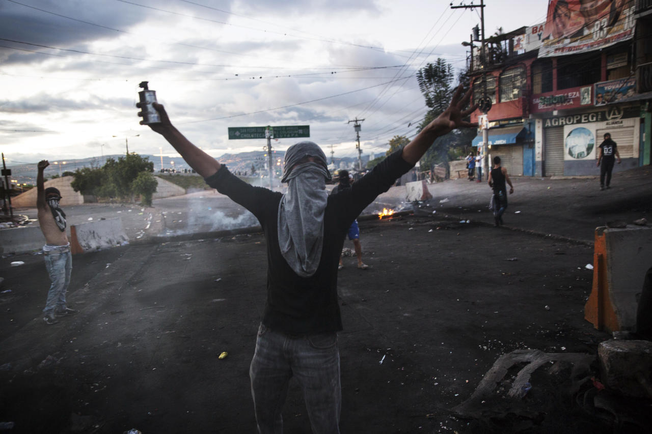 <p>A masked supporter of presidential candidate Salvador Nasralla yells at fellow protesters to fight police at their roadblock to protest what they call electoral fraud in Tegucigalpa, Honduras, Friday, Dec. 1, 2017. (Photo: Rodrigo Abd/AP) </p>