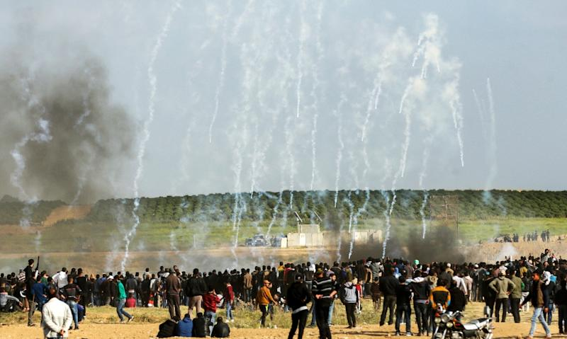 (FILES) In this file photo taken on March 30, 2018 Palestinian protestors run for cover from tear gas fired by Israeli security forces during clashes after a demonstration commemorating Land Day, near the border between Israel and the Gaza Strip