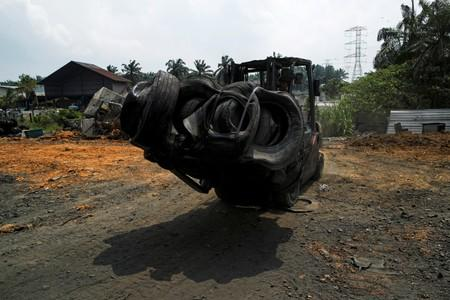 A worker moves a bale of tyres at a tyre pyrolysis plant in Kulai, Johor
