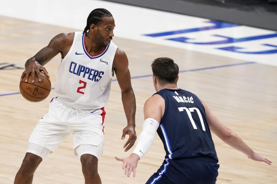 Los Angeles Clippers' Kawhi Leonard (2) looks for an opening to the basket as Dallas Mavericks' Luka Doncic (77) defends in the first half in Game 3 of an NBA basketball first-round playoff series in Dallas, Friday, May 28, 2021. (AP Photo/Tony Gutierrez)