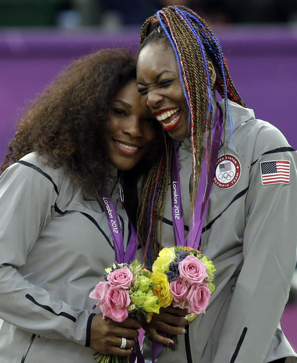 FILE - Serena Williams, left, and Venus Williams of the United States laugh together on the podium after receiving their gold medals in women's doubles at the 2012 Summer Olympics at the All England Lawn Tennis Club in Wimbledon, London, in this Sunday, Aug. 5, 2012, file photo. Serena and Venus Williams, who have a combined nine golds, won't be participating at the Tokyo Games. (AP Photo/Elise Amendola, File)
