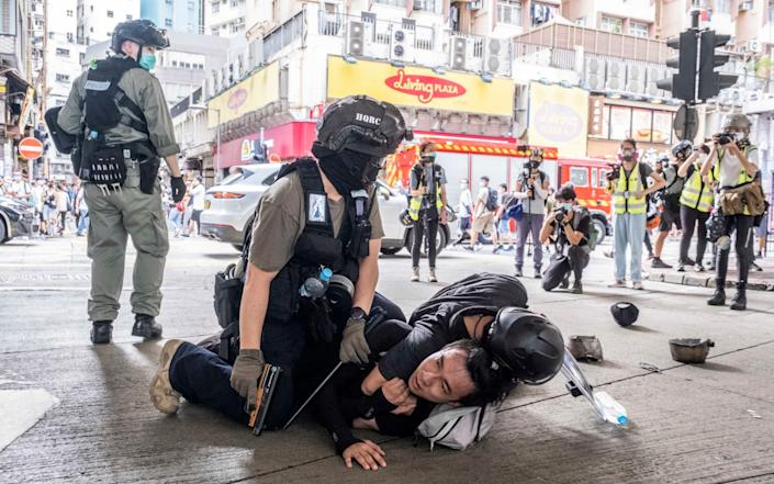Police officers make an arrest during protests in the Causeway Bay neighbourhood of Hong Kong on July 1 after protests greeted China's imposition of its controversial national security law - LAM YIK FEI/ NYTNS / Redux / eyevine