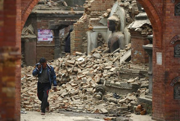 A man cries as he walks on the street while passing through a damaged statue of Lord Buddha. (Reuters)