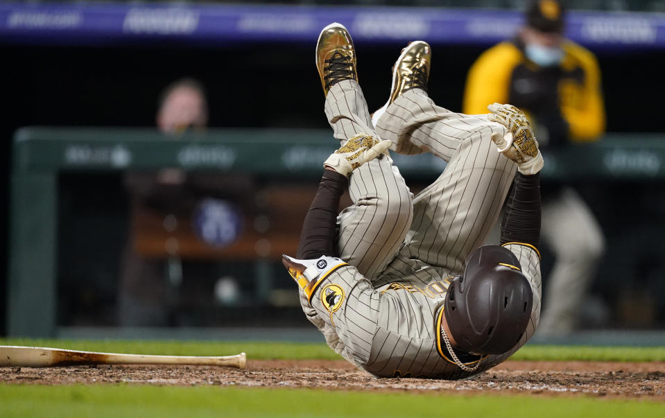 San Diego Padres' Manny Machado falls in the batter's box after fouling a ball off his foot during the eighth inning of the team's baseball game against the Colorado Rockies on Tuesday, May 11, 2021, in Denver. Machado remained in the game. (AP Photo/David Zalubowski)